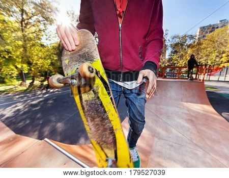 Skateboarder holding a skateboard closeup in the park halfpipe