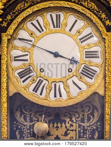 Round dial antique pendulum clock with gilt pattern, filigree hands and Roman numerals