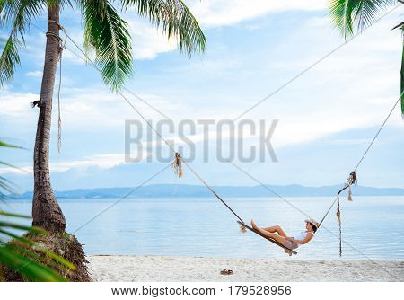 A girl is lying on a swing between two palms. Relaxation and rest.
