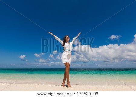 Happy woman with raised arms at tropical beach