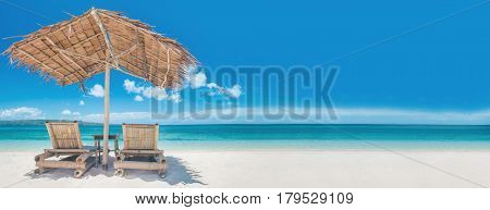 Two bamboo chairs under straw umbrella on tropical beach