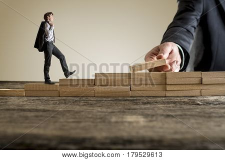 Little businessman walking light up the career ladder while the hand of other man building stairs for him. Wooden bricks and table with copy space.