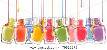 Row of open bottles of nail polish and a jets of dripping lacquer on white background. Close up.