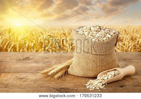 Oat flakes in sack. Ears of oats and oatmeal in bag on table with ripe cereal field on the background. Agriculture and harvest concept. Uncooked porridge. Golden field on sunset