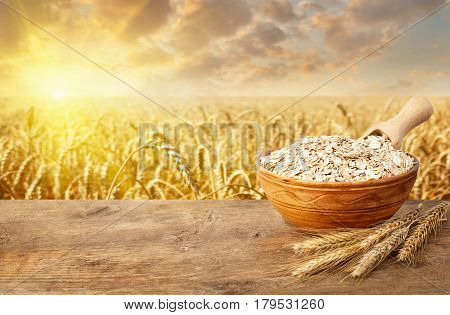 ears of oats and oatmeal in bowl on table with ripe cereal field on the background. Golden field on sunset. Uncooked porridge.  Agriculture and harvest concept