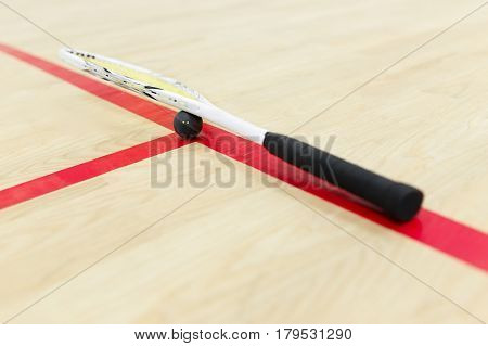 squash racket and ball on the wooden floor. Racquetball equipment for squash game on the court. Photo with selective focus