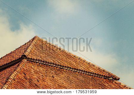 Top of old tile roof against blue sky