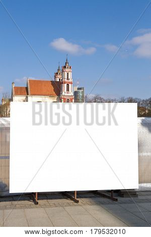 Mock up. Vertical blank billboard outdoors, outdoor advertising, public information board near construction site in the city