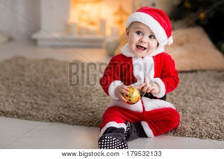 funny baby boy weared in Santa hat with golden Christmas ball, little Santa in the background of the Christmas tree