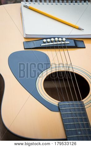 Yellow Acoustic Guitar On Wooden Table stock photo