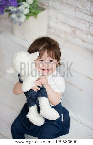 Little girl holding a teddy bear or sheep. Happy child.