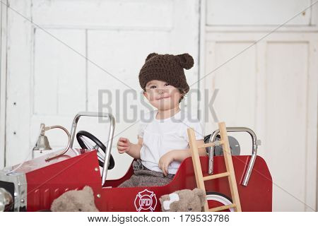 Child riding in red car. Kid smiling in a brown hat