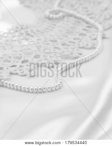 Smooth elegant white silk or satin with pearls and lace can use as wedding background. In black and white toned. Retro style