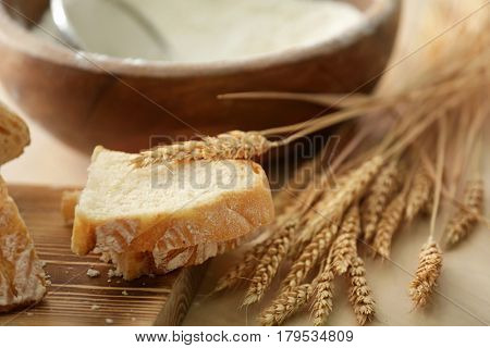 Tasty bread, wooden board and wheat spikelets on kitchen table