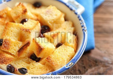 Bowl with delicious bread pudding on table, closeup