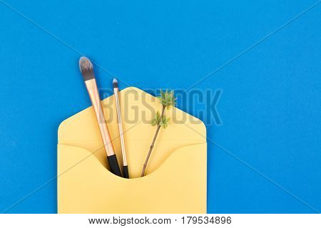 Make up brushes in envelope with first spring gentle leaves and buds on small twigs. Top view