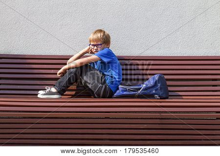 Tired schoolboy with glasses sitting on the bench after school at sunny day