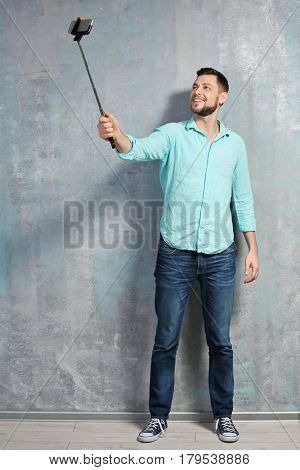 Young man taking selfie while standing near textured wall