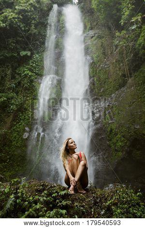 Beautiful woman in red bikini and waterfall.