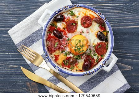 Baking dish with tasty Spanish baked egg, fork and knife on napkin