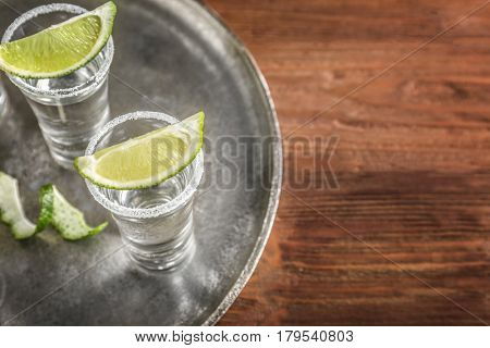 Tequila shots with juicy lime slices and salt on tray