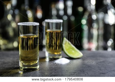 Golden tequila shots with juicy lime and salt on blurred background of glass bottles
