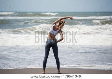 Young sporty woman training on the beach.