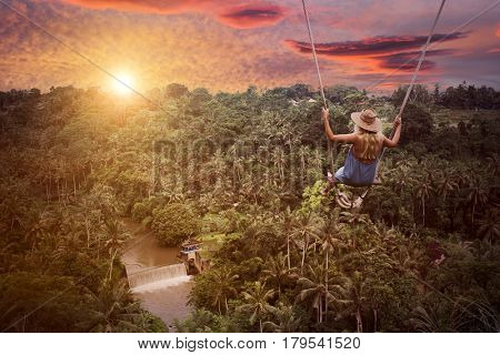 Adventure in wild jungle forest. Woman on swing.