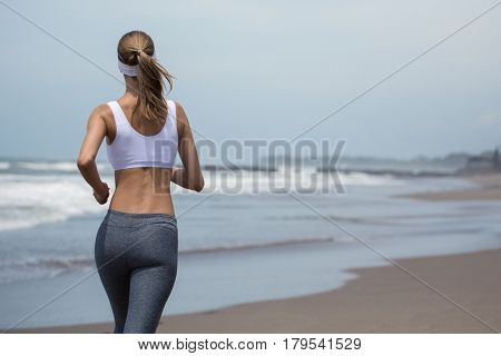 Young sporty woman running on the beach. Back view.