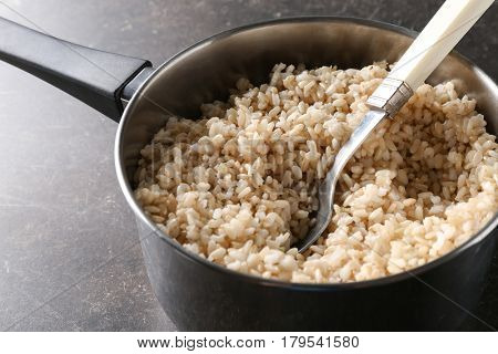 Stewpot full of brown rice saturated with water