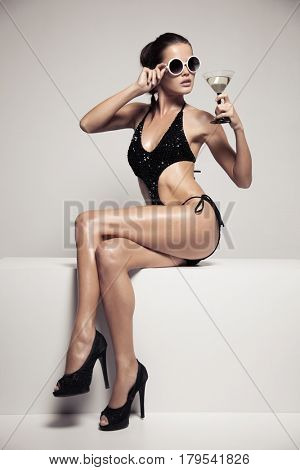 Beautiful woman with glamour make up in stylish black  swimwear. Drink glass cocktail.