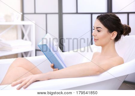 Beautiful young woman reading book while taking bath at home