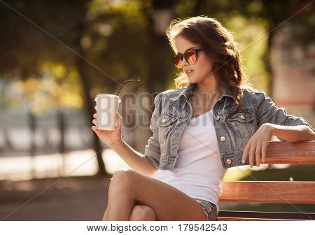 Young woman drinking coffee from paper cup. Sitting on bench in park.