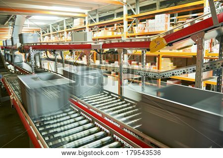 Automated warehouse. Boxes with spare parts moving on conveyer