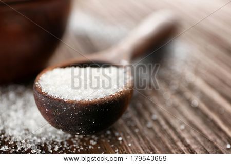 Spoon full of white granulated sugar on wooden background