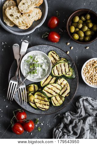 Grilled zucchini olives tomatoes ciabatta - simple snack or appetizer. Mediterranean style food. On a dark background top view. Flat lay