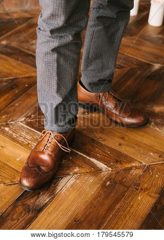 the man's legs in checkered trousers and brown boots loafers on a wooden floor close up. To prepare for wedding. concept of style inspiration. Hipster fashion man's legs.