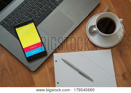 Nitra, Slovakia, march 28, 2017: Snapchat application in a mobile phone screen. Workplace with a laptop, an earphones, notepad, pen and coffee on wooden background