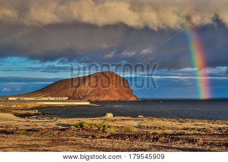 The Rainbow above Montana roja with evening sunlight, Tenerife, Canary Islands