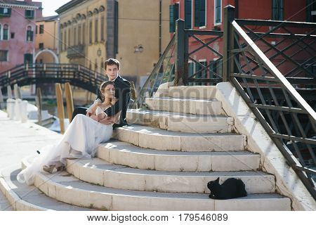 Young couple bride and groom and black cat in Venice Italy