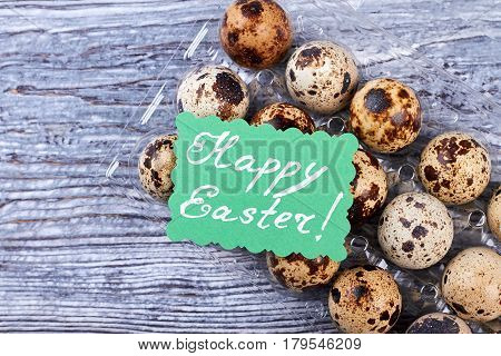Quail eggs, Easter greeting card. Egg tray on gray wood.