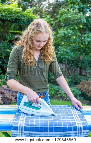 Young european woman ironing tea towel with iron in garden