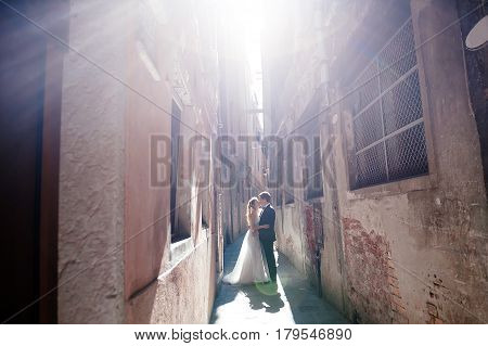 Venice Italy - bride and groom kissing in a sunny wedding day