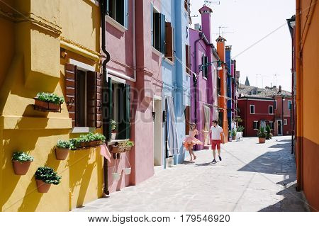 Burano island Venice Italy - happy couple and colorful buildings