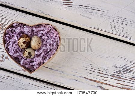 Quail eggs in shredded paper. Top view of heart box. Love and new life.