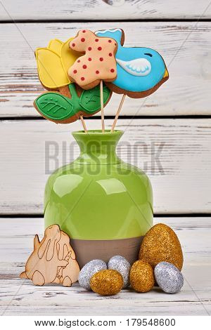 Easter cookies and crafts. Sparkly eggs on wooden surface.