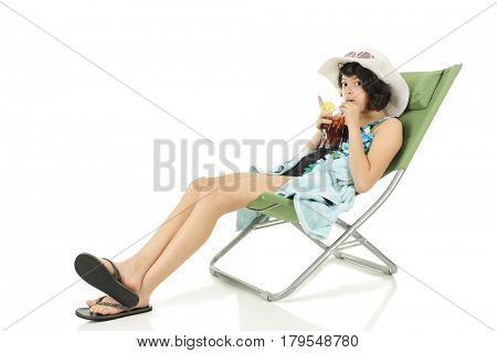 A slim teen girl looking at the viewer as she chills out on a beach chair in her beach outfit and sipping a glass of iced tea.  On a white background with space in upper left for your text.