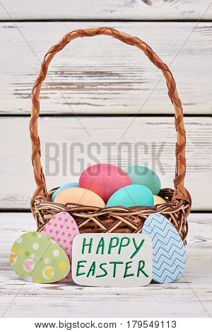 Basket and paper egg cutouts. Easter greeting card.