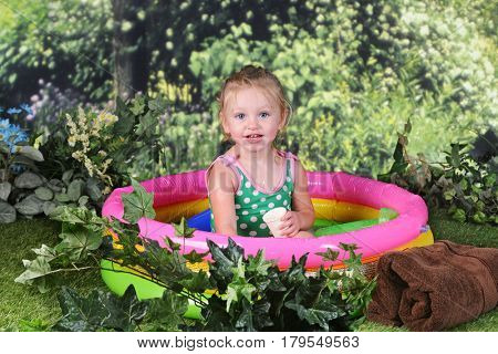 An adorable 2 year old smiling at the viewer as she sits pretty in her kiddie pool on a sunny summer day.