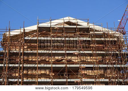 Extensive scaffolding providing platforms for work in progress on a church in restructuring .